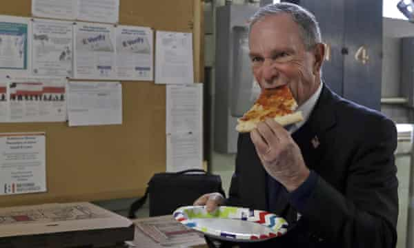 Michael Bloomberg eats a slice of pizza after a tour of the WH Bagshaw Company in Nashua, New Hampshire.