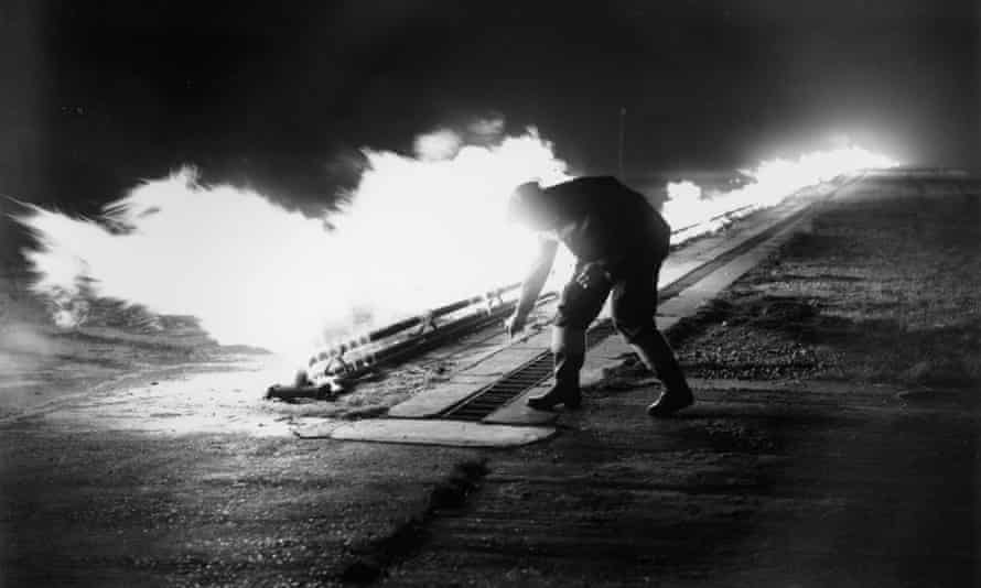 A member of staff at Blackbushe Airport, Surrey ignites burners in preparation for aircraft to take off in fog in November 1952.