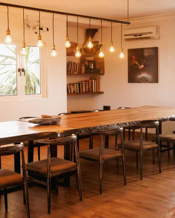 Guests face each other across a long, shared wooden table.