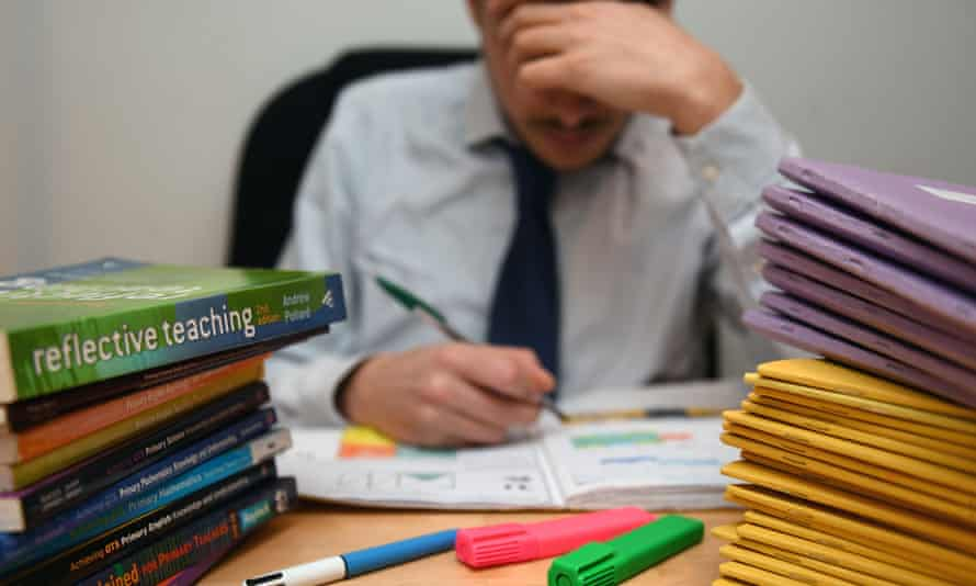 A teacher next to a pile of classroom books.