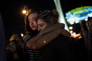 Two women embrace during a candlelit vigil at the junction of Sahara Avenue and Las Vegas Boulevard