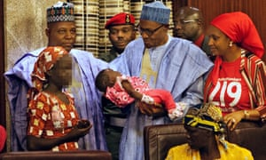 Nigerian president Mohammadu Buhari holds the daughter of the kidnapped Chibok schoolgirl Amina Ali, left.