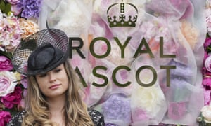 A racegoer poses in front of the flower wall at Royal Ascot.