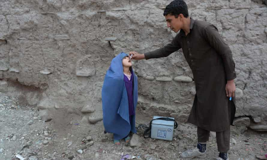An Afghan health worker administers the polio vaccine to a child on the outskirts of Jalalabad