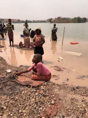 An orphan girl rinses stones to sell to Chinese traders