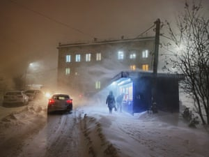 A customer peers into a fish stall as a storm blasts through Murmansk