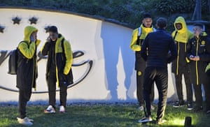 The Dortmund players stand around near to the team bus.