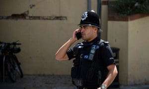 A British police officer talks on the phone without a protective face mask in Gibraltar.