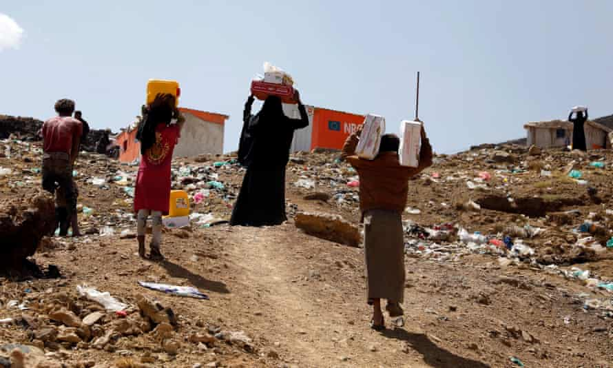 Displaced Yemenis carry food rations provided by a charitable organisation at a camp in Sana'a, Yemen