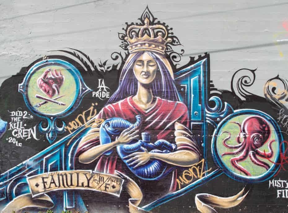 Graffiti mars a mural in a Highland Park parking lot.