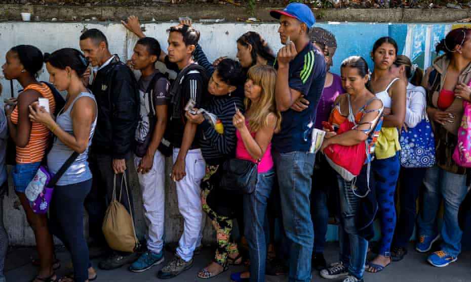 People queue to buy basic food and household items outside a supermarket in Caracas.
