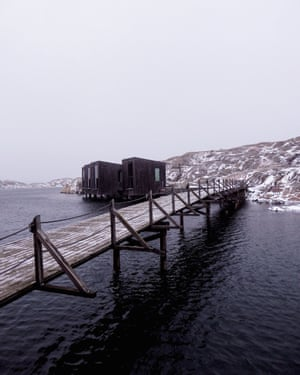 Amid icy conditions, a walkway across water leads to wooden buildings that are part of the Nordic Watercolour Museum in Bohuslän, Sweden.
