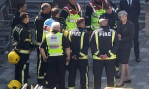 Prime minister Theresa May with members of the fire service at Grenfell Tower.