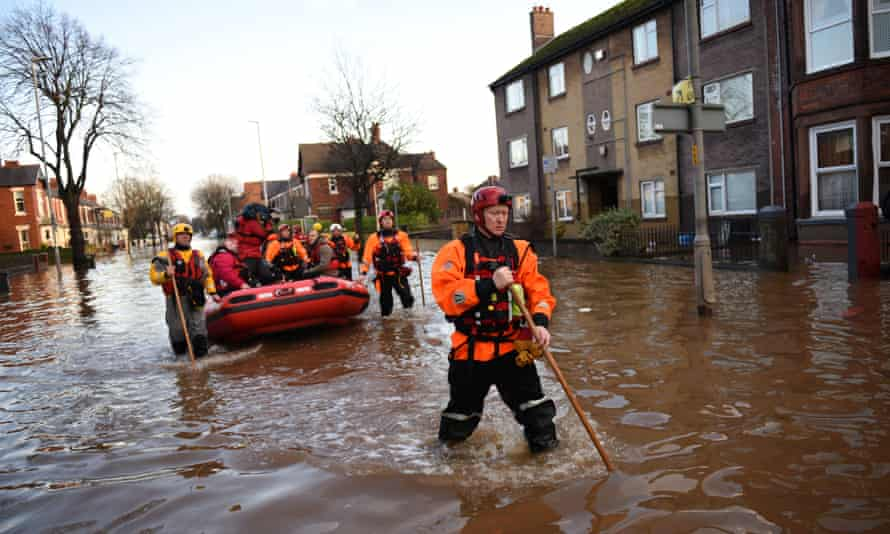 Members of the emergency services rescue residents from their flooded properties in Carlisle