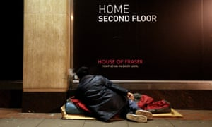 Homeless person in front of a shopfront sign reading 'Home second floor'.