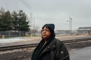 Zulene Mayfield stands on the street she used to live on in Chester, Pennsylvania. Behind her is the Covanta incinerator.