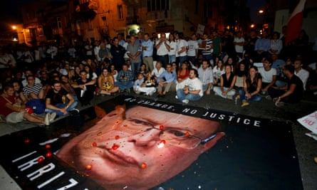 Protesters in 2017 throw tomatoes and coins on a banner calling on then Malta police commissioner, Lawrence Cutajar, to resign.
