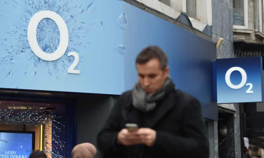 Man uses phone while walking past O2 shop