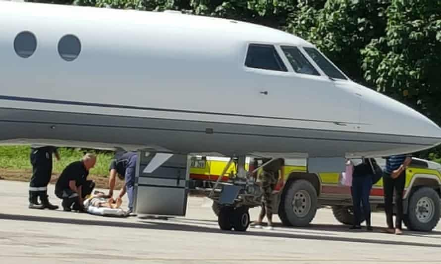 A critically-ill Iranian child refugee known as M is seen being transferred to a plane to be brought to Australia from Nauru with his family on Tuesday.