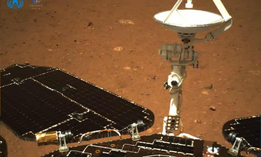 An image taken by a camera on the rear of China's Zhurong rover on the surface of Mars, showing the rover's solar panels and antenna.