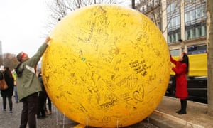 Activists write on a sphere during a demonstration near the Arc de Triomphe.