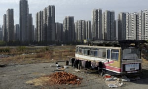 A couple in Hefei converted a bus into a home near newly-constructed residential buildings in Hefei.