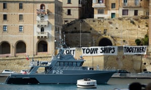 A Malta Coast Guards ship patrols as protesters display a banner urging action on migrant rescue.
