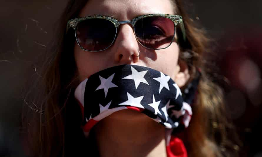 A protester wears a patriotic bandana over her mouth during the Women's March on 8 March 2017 in Washington DC.