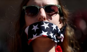 International Women's Day Marked With Rallies And Protests Across The Country<br>WASHINGTON, DC - MARCH 08:  A protester wears a patriotic bandana over her mouth during a march and rally to support women's health programs and protest the White House global gag rule on March 8, 2017 in Washington, DC. Hundreds of women marked International Women's Day with a march and rally outside of the White House to protest the White House global gag rule and support women's health programs.  (Photo by Justin Sullivan/Getty Images)
