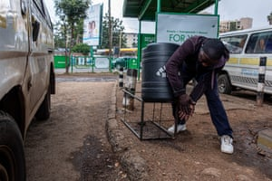 A man washes his hands before getting into a matatu bus