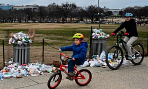 People bike past overflowing trash cans on the National Mall in Washington, DC.