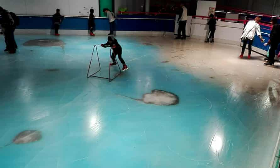 Skaters on the rink at Space World in Kitakyushu with enlarged photos of rays under the ice.