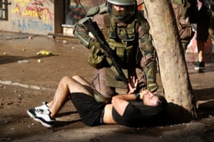 A police officer detains a protester in Santiago, Chile