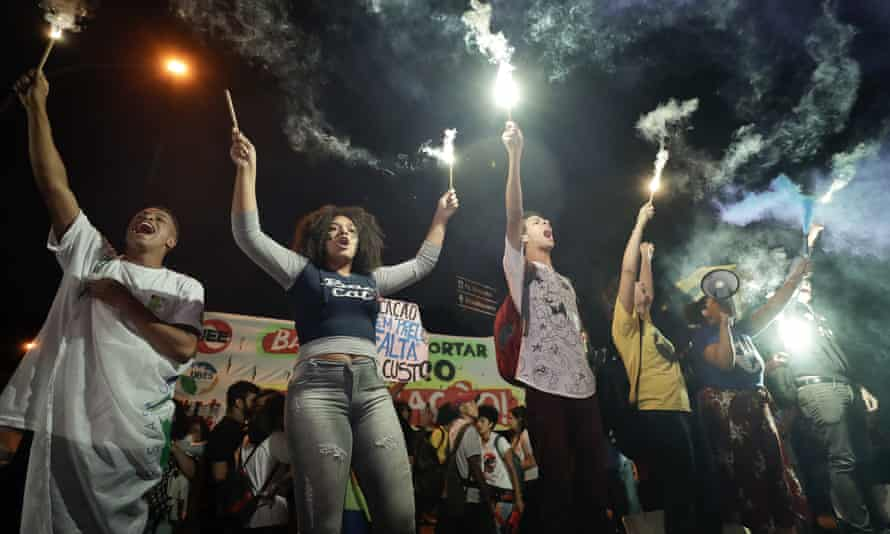 Students light flares as they protest against a massive cut in the education budget imposed by Jair Bolsonaro.