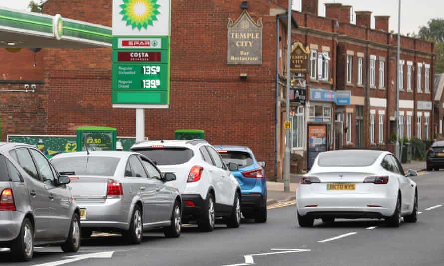 A Tesla electric car drives past cars queueing for fuel at a BP filling station in Peterborough
