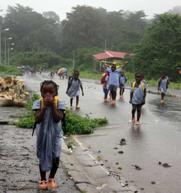 Children are caught in a tropical downpour in Santiago de Baney on Bioko island.