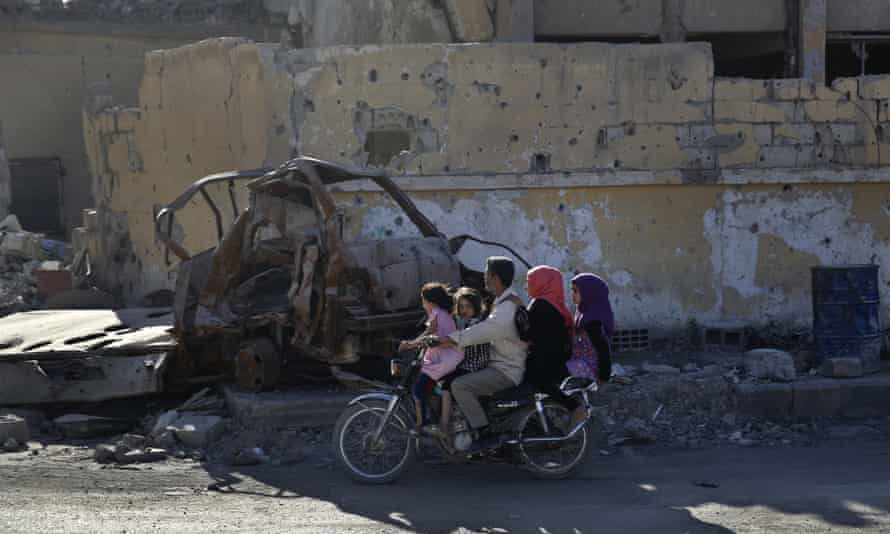 a family rides a motorcycle on a street that was damaged during fighting, Raqqa, Syria.