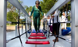 84-year-old Zady Jones walks across a rope step bridge at the senior playground at Carbide Park