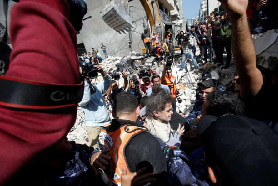 Rescuers carry Suzy Eshkuntana, 6, as they pull her from the rubble of a building at the site of Israeli air strike in Gaza City.
