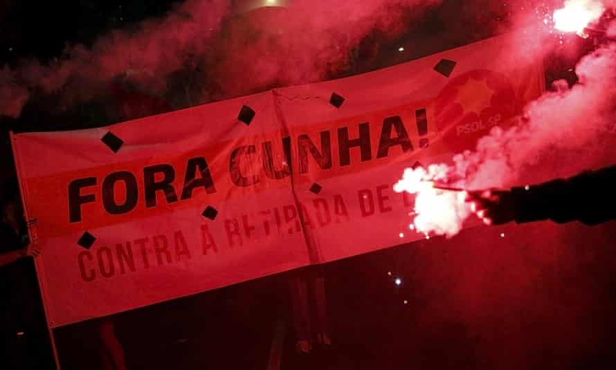 """Demonstrators hold a banner that reads, """"out Cunha"""", as they march in a rally supporting Brazilian president Dilma Rousseff in Sao Paulo, Brazil."""