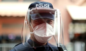 A municipal police officer wearing protective face mask stands guard at Forville market in Cannes, France, 25 April 2020.