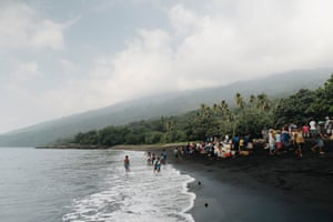Residents living temporarily at Lone evacuation area, West Ambae, gather on the beach with their belongings, waiting for a privately arranged ship to transport them to nearby island, Espirito Santo. The black sand beach was a rocky coastline seven months ago, however intensifying activity and heavy ashfall from the Manarao Volcano has rapidly changed the coastline appearance.