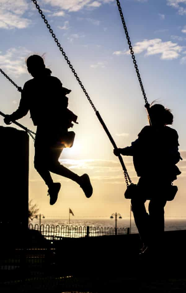 Silhouette of two female children playing on swings against a blue sky with the sun beginning to set