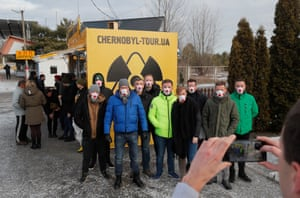 Visitors take a photo in front of a souvenir shop wall with a radiation symbol at the Dytyatky checkpoint of the Chernobyl Exclusion Zone, Ukraine