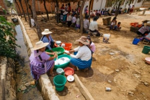 Women wash dishes by the open canal
