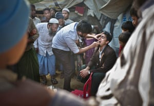 Cox's Bazar, BangladeshA big crowd is holding its breath as a dentist is putting a fake tooth inside the mouth of his patient. Two dollars for a tooth to smile again. Life carries on at Kutapalong camp
