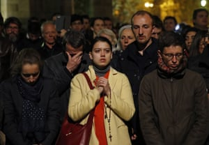 People pray as Notre Dame cathedral burns in Paris.