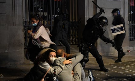 Riot police in Barcelona use batons to disperse protests against Covid restrictions.
