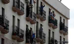 People wave from their balconies as they celebrate Palm Sunday during the coronavirus lockdown, in Ronda, southern Spain.