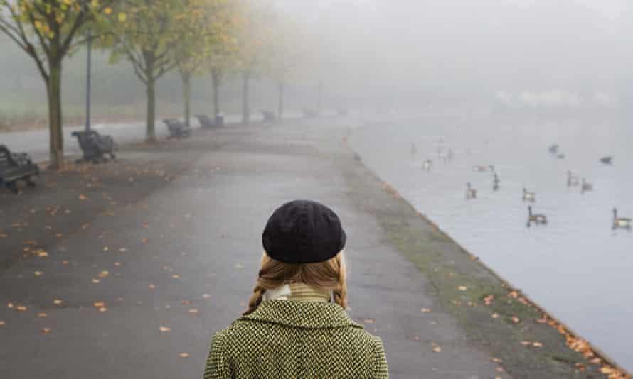 Woman walking in a foggy park